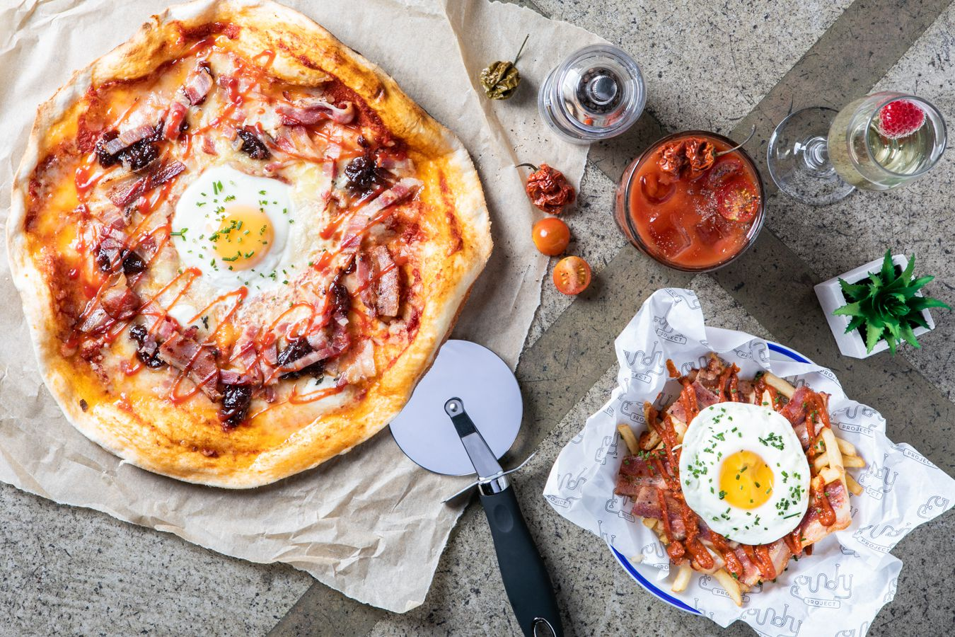 A pizza with a side of chips with bacon topped with fried egg